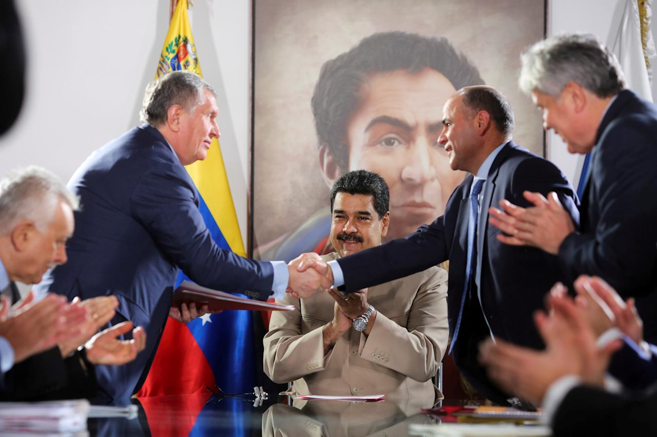 Head of Russian state oil firm Rosneft Igor Sechin (standing L) shakes hands with Venezuela's Oil Minister and President of the Venezuelan state oil company PDVSA Manuel Quevedo, in front of  Venezuela's President Nicolas Maduro, in Maiquetia, Venezuela December 16, 2017. Miraflores Palace/Handout via REUTERS   ATTENTION EDITORS - THIS PICTURE WAS PROVIDED BY A THIRD PARTY     TPX IMAGES OF THE DAY