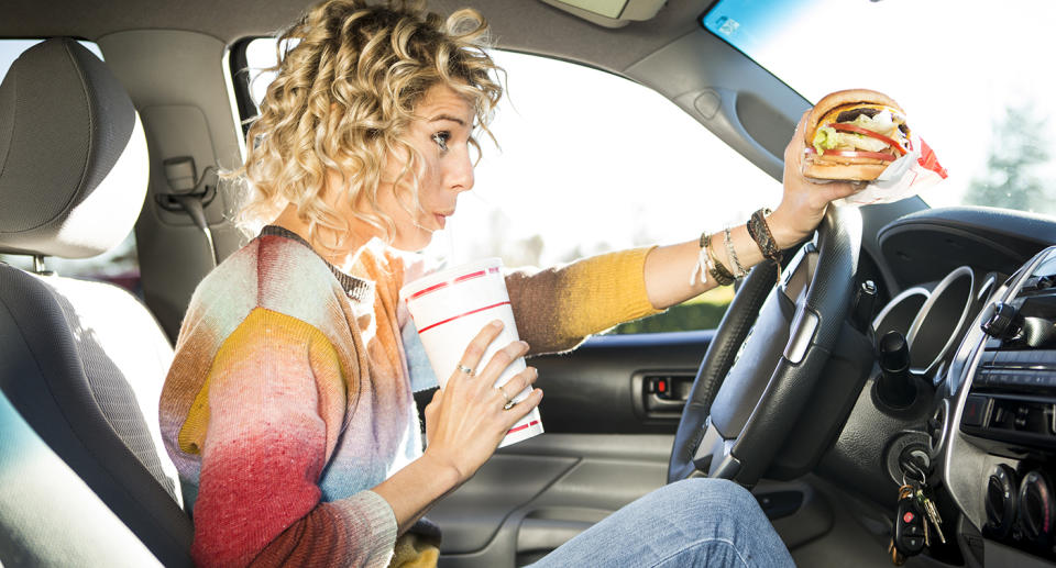 A woman eating burgers from a fast food chain while driving a car. Source: Getty Images