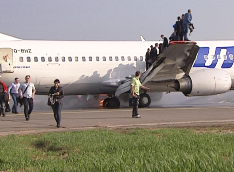 In this image taken Saturday, May 18, 2013 made available from AP video, passengers leave a Boeing 737 belonging to Russian carrier UTair in Vnukovo airport, outside , Russia, on Saturday, May 18, 2013. Emergency officials said the landing gear of a plane carrying more then 130 people caught on fire as it was landing. All passengers and crew members were safely evacuated. (AP Photo/AP video)