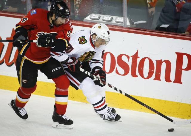 Chicago Blackhawks' Marian Hossa, right, from Slovakia, battle Calgary Flames' David Jones for the puck during first period NHL hockey action in Calgary, Canada, Tuesday, Jan. 28, 2014. (AP Photo/The Canadian Press, Jeff McIntosh)