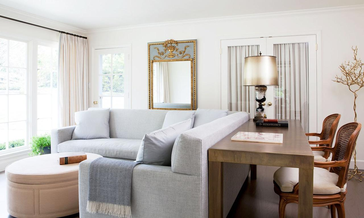 """<p>Here, <a href=""""https://heatherhilliard.com/"""" target=""""_blank"""">Heather Hilliard</a> opted for a roomy and inviting sectional in a light blue sitting room. The upholstered ottoman contributes to the comfy environment while the ornate gilt mirror is all it takes to dress up the room without making it feel stuffy. </p>"""
