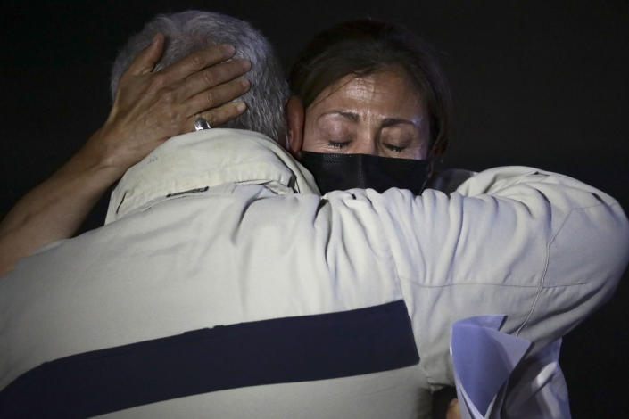 Former Colombian Presidential candidate Ingrid Betancourt, right, who was abducted while campaigning by the Revolutionary Armed Forces of Colombia, FARC, rebels, is comforted by another kidnapping victim during an event at the Truth Commission to commemorate victims of the country's decades-long armed conflict, in Bogota, Colombia, Wednesday, June 23, 2021. (AP Photo/Ivan Valencia)