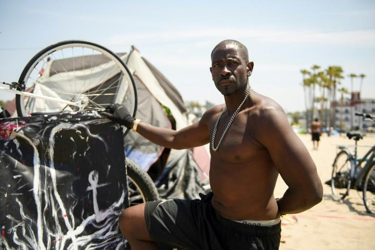 Rodrick Mims, 50, kneels for a portrait next to his artwork and tent shelter at Venice Beach