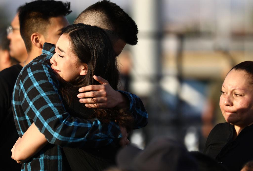 Mourners embrace at a vigil honoring Horizon High School sophomore Javier Amir Rodriguez, who lost his life in a mass shooting in nearby El Paso, on August 5, 2019 in Horizon City, Texas. The vigil was held at the school's football field.   Mario Tama—Getty Images
