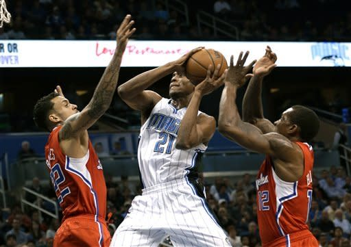Orlando Magic's Moe Harkless (21) gets between Los Angeles Clippers' Matt Barnes, left, and Eric Bledsoe for a shot during the first half of an NBA basketball game, Wednesday, Feb. 6, 2013, in Orlando, Fla. (AP Photo/John Raoux)