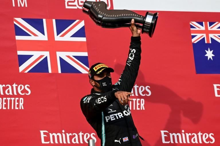 End game? Lewis Hamilton holds his trophy as he celebrates winning on Sunday