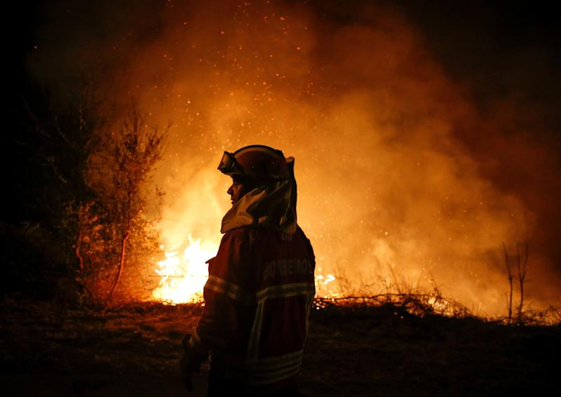 A firefighter stands silhouetted against the flames in Cabanoes near Lousa, Portugal, on Oct. 16, 2017.