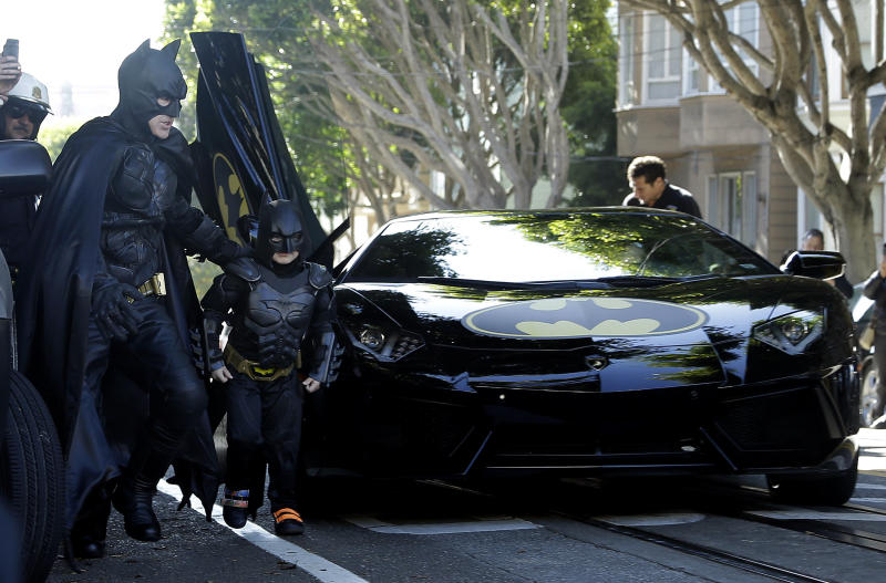 """Miles Scott, dressed as Batkid, second from left, exits the Batmobile with Batman to save a damsel in distress in San Francisco, Friday, Nov. 15, 2013. San Francisco turned into Gotham City on Friday, as city officials helped fulfill Scott's wish to be """"Batkid.""""Scott, a leukemia patient from Tulelake in far Northern California, was called into service on Friday morning by San Francisco Police Chief Greg Suhr to help fight crime, The Greater Bay Area Make-A-Wish Foundation says. (AP Photo/Jeff Chiu)"""