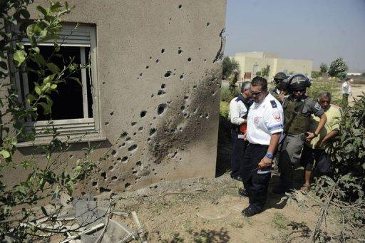 An Israeli paramedic and border police survey the damage caused by a rocket launched from the Gaza Strip and which hit the Saad Kibbutz in southern Israel. The military wing of Hamas said late on Wednesday it had agreed to an Egyptian-brokered ceasefire with Israel, after three days of bloodshed in and around Gaza