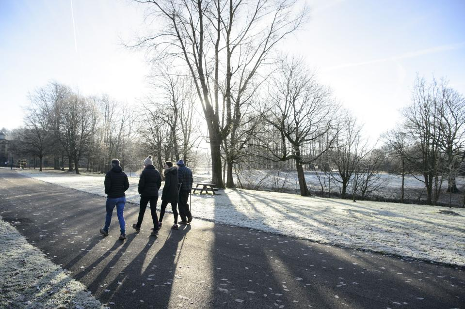 People stroll in widespread frost in Glasgow's Pollok Park, as temperatures plummet across the UK.