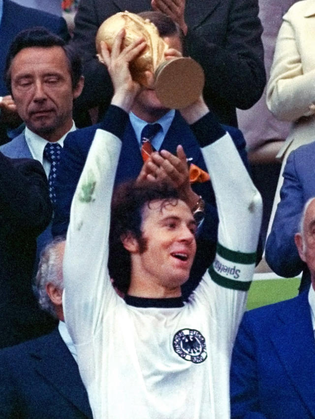 FILE - In this July 7, 1974 file photo, West Germany's Franz Beckenbauer, holds up the World Cup trophy after they defeated the Netherlands 2-1 in the World Cup soccer final at Munich's Olympic stadium in Germany. With one week to go before the World Cup starts in Brazil, The Associated Press takes a look at 10 great stars in the tournament's history. Beckenbauer defined the role of libero and his elegant and effortless style earned him the nickname the Kaiser. Beckenbauer won every club honor with Bayern Munich, including three straight Champions Cup titles, and is the only man to captain (in 1974) and coach (1990) a team to the World Cup title. Beckenbauer made 103 appearances for Germany and is considered the football power's best player of all time. He also served as coach and president of Bayern. At 68, he has given up official functions but still works for television and remains vastly popular in Germany. (AP Photo/File)