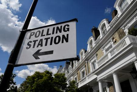 A polling station direction sign is seen placed on a lamppost, ahead of the forthcoming EU elections, in London, Britain, May 21, 2019. REUTERS/Toby Melville