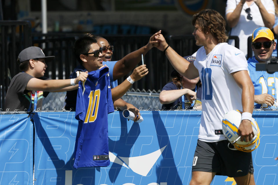 Los Angeles Chargers quarterback Justin Herbert, right, high fives fans after practice at the NFL football team's training camp in Costa Mesa, Calif., Wednesday, July 28, 2021. (AP Photo/Alex Gallardo)