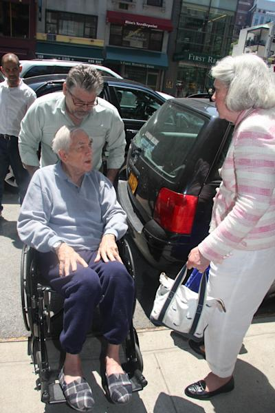 An unidentified man pushes Anthony Marshall in a wheelchair while his wife, Charlene Marshall speaks to him on Friday, June 21, 2013, in New York. Marshall, the 89-year-old son of the late philanthropist Brooke Astor, was on his way to court and possibly prison to begin serving a one-to-three year sentence for stealing from his mother in the final years of her life. (AP Photo/William Regan)