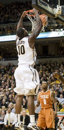 Missouri's Ricardo Ratliffe, left, dunks the ball over Texas' Julien Lewis, right, for two of his team-high 21 points during the second half of an NCAA college basketball game Saturday, Jan. 14, 2012, in Columbia, Mo. Missouri won the game 84-73. (AP Photo/L.G. Patterson)