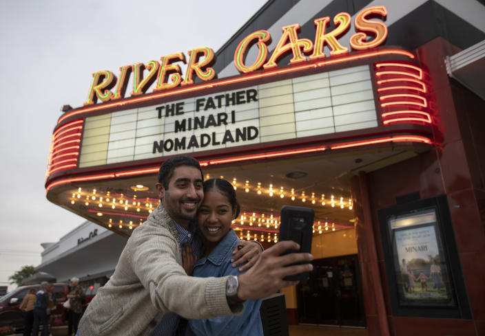 """Jeet Singh and Rubi Morgan take a selfie with the River Oaks Theatre marquee after watching """"Minari"""" on the second last day of the theater Wednesday, March 24, 2021, in Houston. The pair was going to buy tickets of the last screening of the theater, but the show was sold out so they picked the second last day. (Yi-Chin Lee/Houston Chronicle via AP)"""