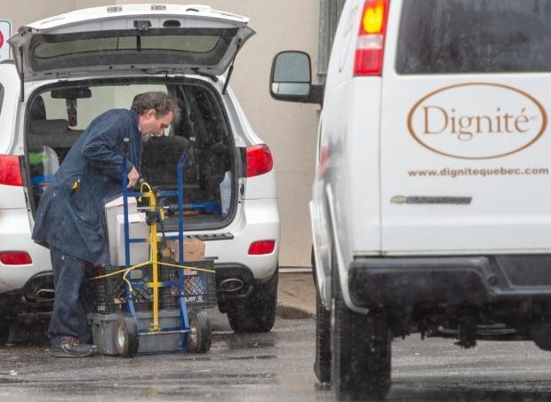 A man unloads supplies at CHSLD Herron on April 13, 2020, while a funeral services vehicle is parked in the foreground. By that point, 31 residents had died during the pandemic crisis. (Ryan Remiorz/The Canadian Press - image credit)