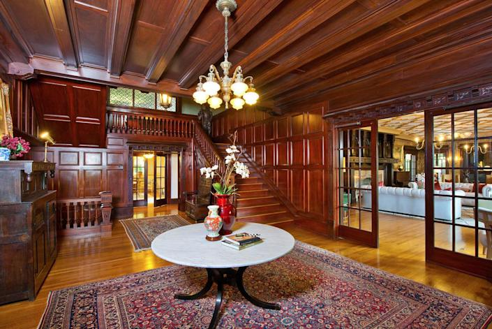 <p>The entry hall reveals original mahogany paneling and restored leaded glass windows.</p>