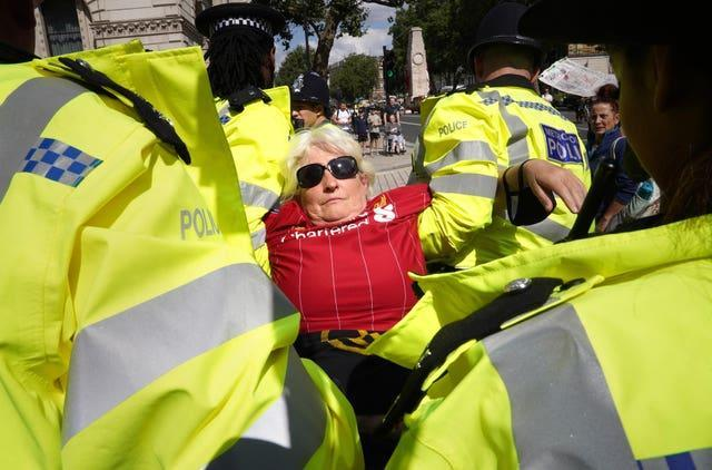 A demonstrator is carried away by police during a protest by members of Extinction Rebellion on Whitehall
