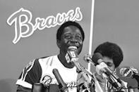 FILE - Atlanta Braves' Hank Aaron smiles during a press conference at Atlanta Stadium, Ga., after the game in which he hit his 715th career home, in this April 8, 1974, file photo. With him is his wife Billye, partially obscured. Hank Aaron, who endured racist threats with stoic dignity during his pursuit of Babe Ruth's home run record and gracefully left his mark as one of baseball's greatest all-around players, died Friday. He was 86. The Atlanta Braves, Aaron's longtime team, said he died peacefully in his sleep. No cause was given. (AP Photo/File)