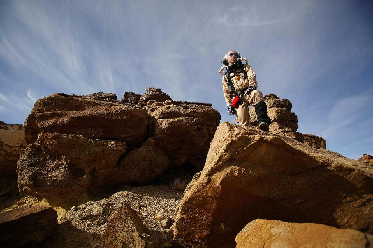 ÷Hans van Ot Woud, a mapping researcher and the health and safety officer of Crew 125 EuroMoonMars B mission, collects geologic samples for study at the Mars Desert Research Station (MDRS) outside Hanksville in the Utah desert March 2, 2013. The MDRS aims to investigate the feasibility of a human exploration of Mars and uses the Utah desert's Mars-like terrain to simulate working conditions on the red planet. Scientists, students and enthusiasts work together developing field tactics and studying the terrain. All outdoor exploration is done wearing simulated spacesuits and carrying air supply packs and crews live together in a small communication base with limited amounts of electricity, food, oxygen and water. Everything needed to survive must be produced, fixed and replaced on site. Picture taken March 2, 2013. REUTERS/Jim Urquhart