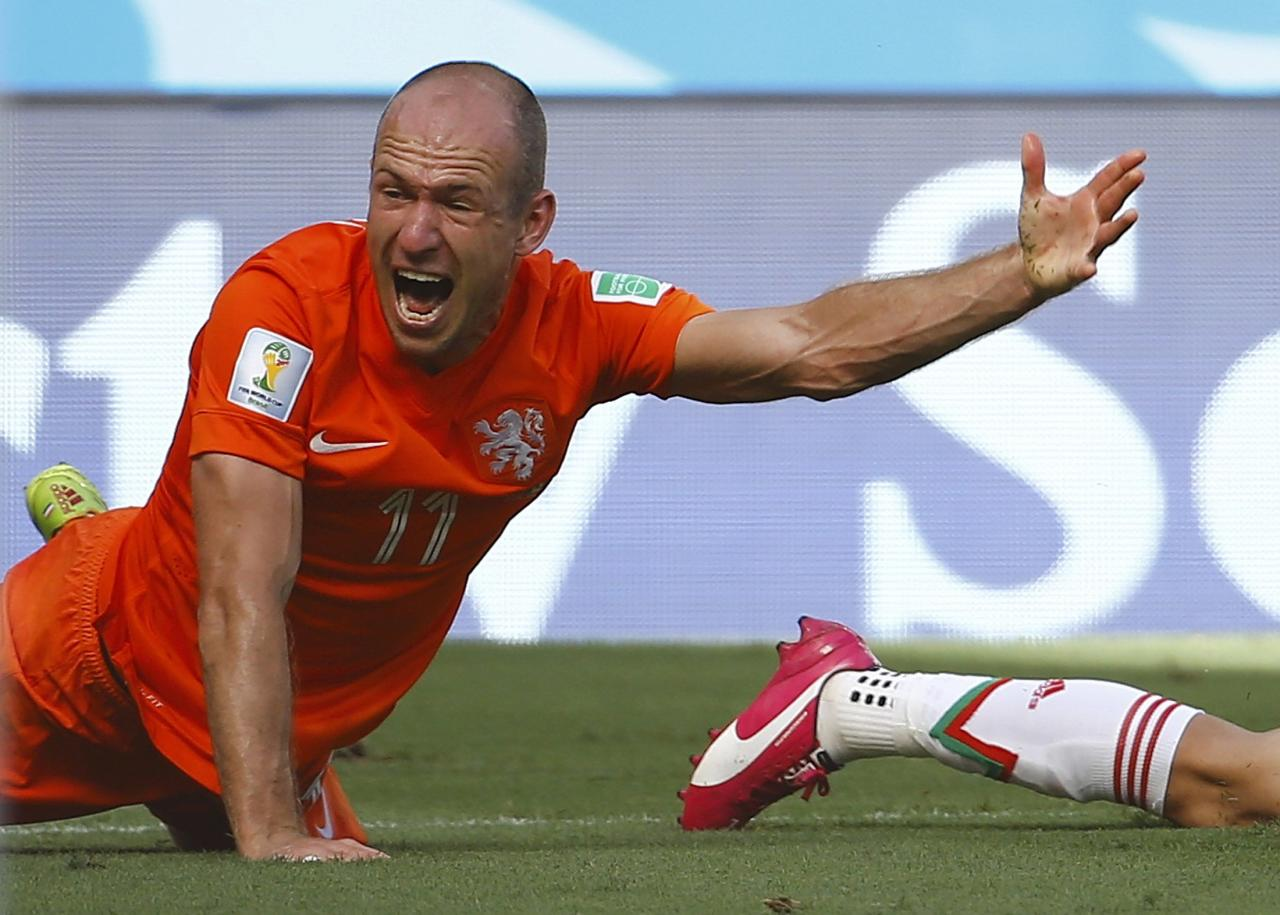 Arjen Robben of the Netherlands reacts after being tackled by Mexico's Miguel Layun during their 2014 World Cup round of 16 game at the Castelao arena in Fortaleza June 29, 2014. REUTERS/Dominic Ebenbichler (BRAZIL - Tags: SOCCER SPORT WORLD CUP) TOPCUP
