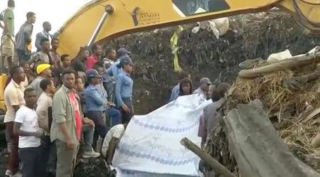 People gather at the site after a landslide at a garbage dump on the outskirts of Addis Ababa, Ethiopia in this still image taken from a video