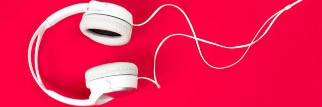 white headphones on red surface
