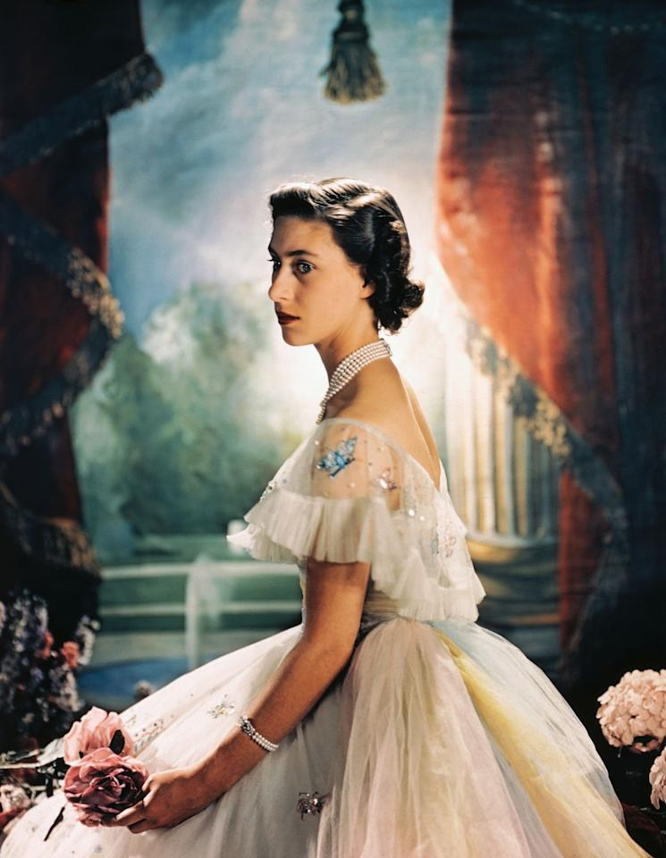 <p>The Princess sits for a royal portrait in 1944, wearing a formal evening dress with sequined butterflies around the shoulder, and holding two pink roses.</p>