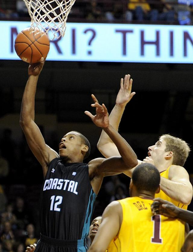 Coastal Carolina forward Michel Enanga (12) shoots against Minnesota guard Andre Hollins (1) and center Elliott Eliason (55) during the first half of an NCAA college basketball game in Minneapolis on Tuesday, Nov. 19, 2013. (AP Photo/Hannah Foslien)