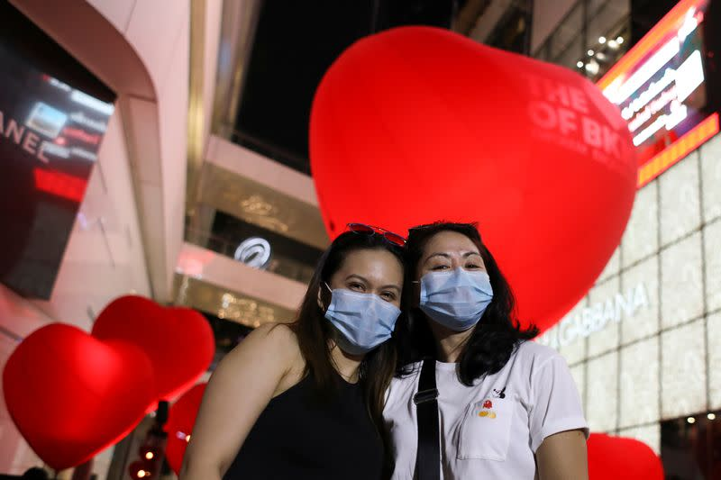 Women wearing protective poses in front of hearts celebrating Valentine's Day in front of shopping mall in Bangkok