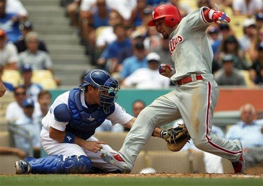 Philadelphia Phillies' Shane Victorino scores on a Carlos Ruiz single as Los Angeles Dodgers as catcher A.J. Ellis applies the late tag in the fourth inning of a baseball game in Los Angeles, Wednesday, July 18, 2012. (AP Photo/Reed Saxon)