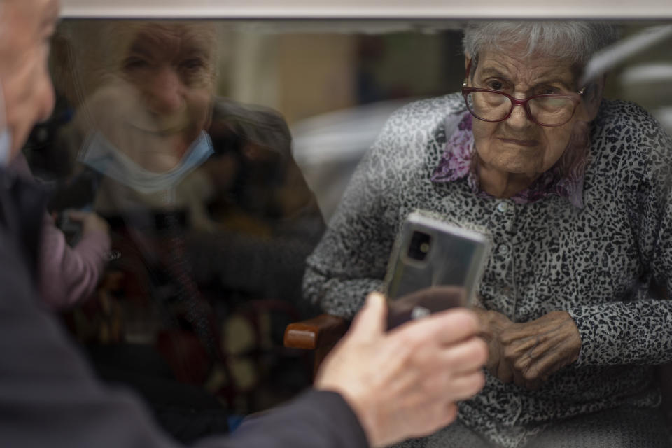 Javier Anto, 90, shows photos of their grandchildren to his wife Carmen Panzano, 92, to combat the ravages of Alzheimer's through the window separating the nursing home from the street in Barcelona, Spain, Wednesday, April 21, 2021. Since the pandemic struck, a glass pane has separated _ and united _ Javier and Carmen for the first prolonged period of their six-decade marriage. Anto has made coming to the street-level window that looks into the nursing home where his wife, since it was closed to visits when COVID-19 struck Spain last spring. (AP Photo/Emilio Morenatti)