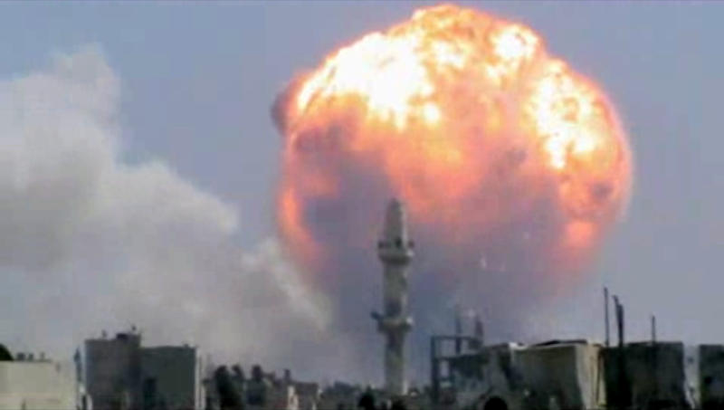 FILE - This Monday, July 15, 2013, file image taken from leaked video obtained by Ugarit News, which has been authenticated based on its contents and other AP reporting, purports to show a fireball from an explosion at a weapons depot set off by rocket attacks that struck government-held districts in the central Syrian city of Homs. Never in history has a war been covered in the way that Syria's civil war has: A constant stream of hundreds of thousands of videos instantaneously bringing all the viciousness, brutality and gore instantaneously and vividly to millions of viewers across the globe via YouTube and social media. The raw footage from Syria's battlefields comes in a perpetual stream _ a vicious civil war brought instantaneously to millions of viewers across the globe via YouTube and social media.(AP Photo/Ugarit News via AP video)