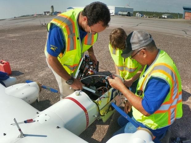 Crew members from the Alaska Center for Unmanned Aircraft Systems Integration examine the inside of the SeaHunter. This is during the two weeks they were taking the photos of the Inuvik to Tuktoyaktuk Highway and portions of the Dempster Highway.