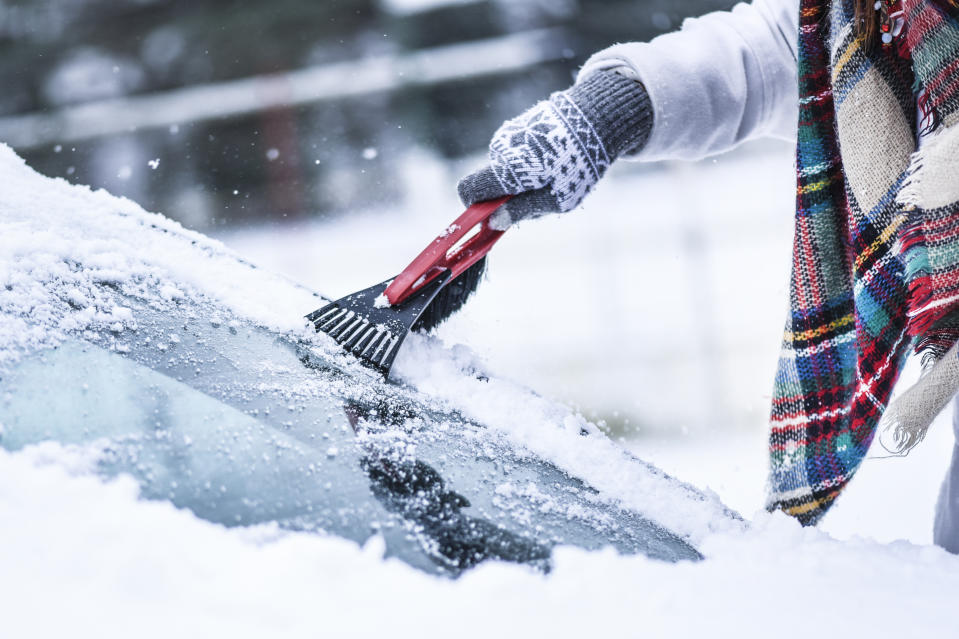 Woman cleaning snow from windshield,