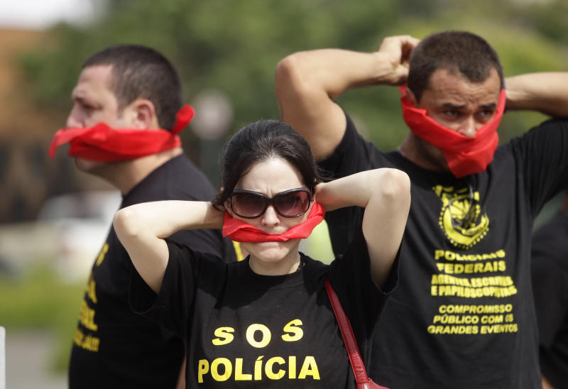 """Federal police wearing T-shirts that read in Portuguese """"SOS Federal Police"""" cover their mouths with bandanas as a way to protest their leaders' recommendation to not protest, as they demand better labor conditions outside the venue where Brazil's coach is announcing his squad for the upcoming World Cup in Rio de Janeiro, Brazil, Wednesday, May 7, 2014. Federal police are threatening to go on strike during the international soccer tournament if their demands are not met. (AP Photo/Silvia Izquierdo)"""