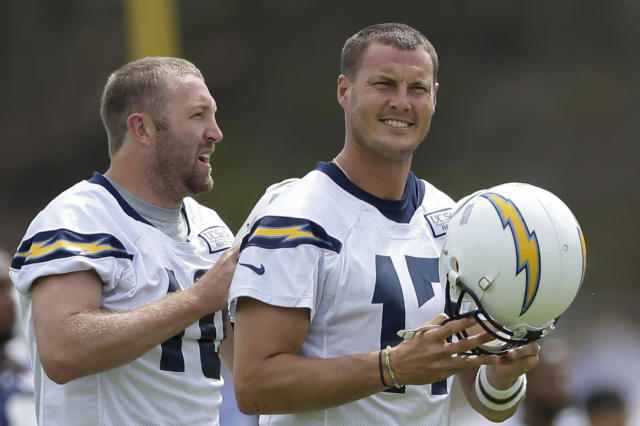 San Diego Chargers quarterback Philip Rivers, right, walks in front of quarterback Kellen Clemens at an NFL football training camp Friday, July 25, 2014, in San Diego. (AP Photo)