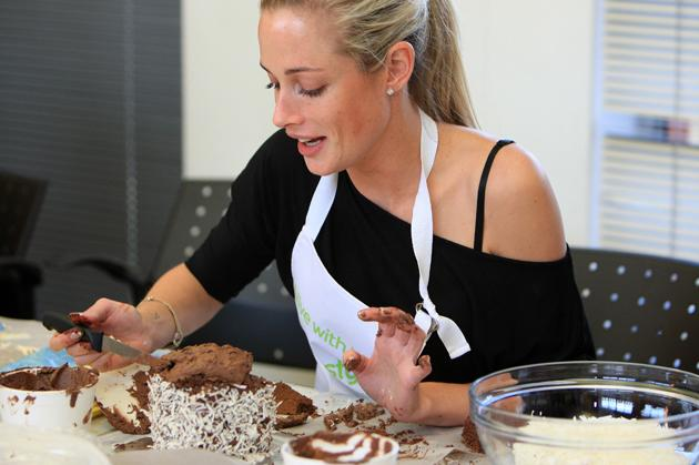<p>Reeva Steenkamp with the cake she baked at the BBC Lifestyle launch of 'Bake-Off' (Gallo Images / Rex Features)</p>