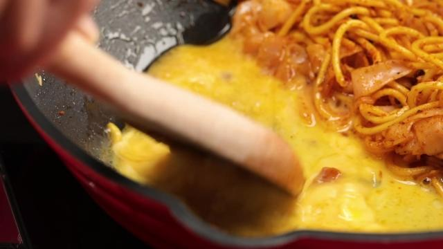 Scrambling eggs beside noodles in the same pan with wooden spatula