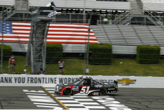 Brandon Jones takes the checker flag as he crosses the finish line to win the NASCAR Truck Series auto race at Pocono Raceway, Sunday, June 28, 2020, in Long Pond, Pa. (AP Photo/Matt Slocum)