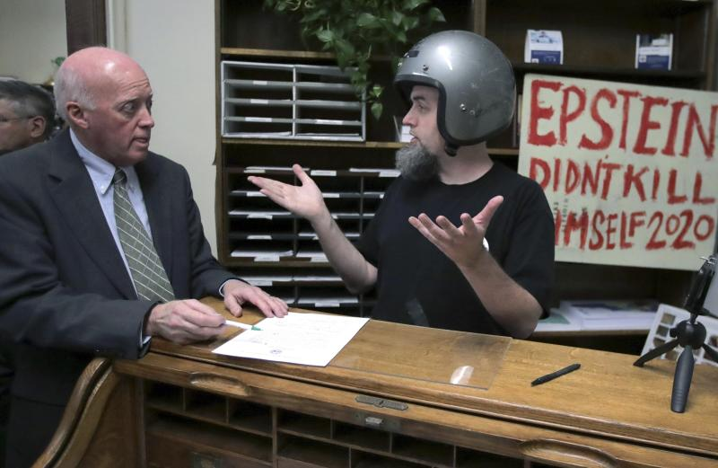 FILE - In this Friday, Nov. 8, 2019, file photo, a candidate who called himself Rod Epstein Didn't Kill Himself Webber attempts to file to be listed on the New Hampshire primary ballot in Concord, N.H. New Hampshire Secretary of State Bill Gardner, left, did not accept the application since he did not file using his legal name. The quadrennial chaos has quieted down over at the New Hampshire secretary of state's office with the closing of the filing period for the first-in-the-nation presidential primary. (AP Photo/Charles Krupa, File)