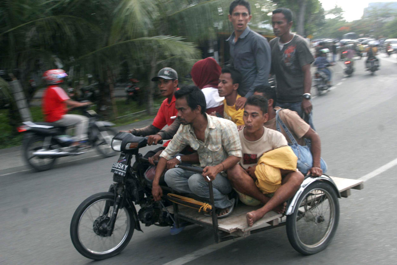 Acehnese men ride on a motorized pedicab as they evacuate to higher ground after a strong earthquake was felt in Banda Aceh, Aceh province, Sumatra island, Indonesia, Wednesday, April 11, 2012. Two massive earthquakes triggered back-to-back tsunami warnings for Indonesia on Wednesday, sending panicked residents fleeing to high ground in cars and on the backs of motorcycles. There were no signs of deadly waves, however, or serious damage, and a watch for much of the Indian Ocean was lifted after a few hours. (AP Photo/Heri Juanda)