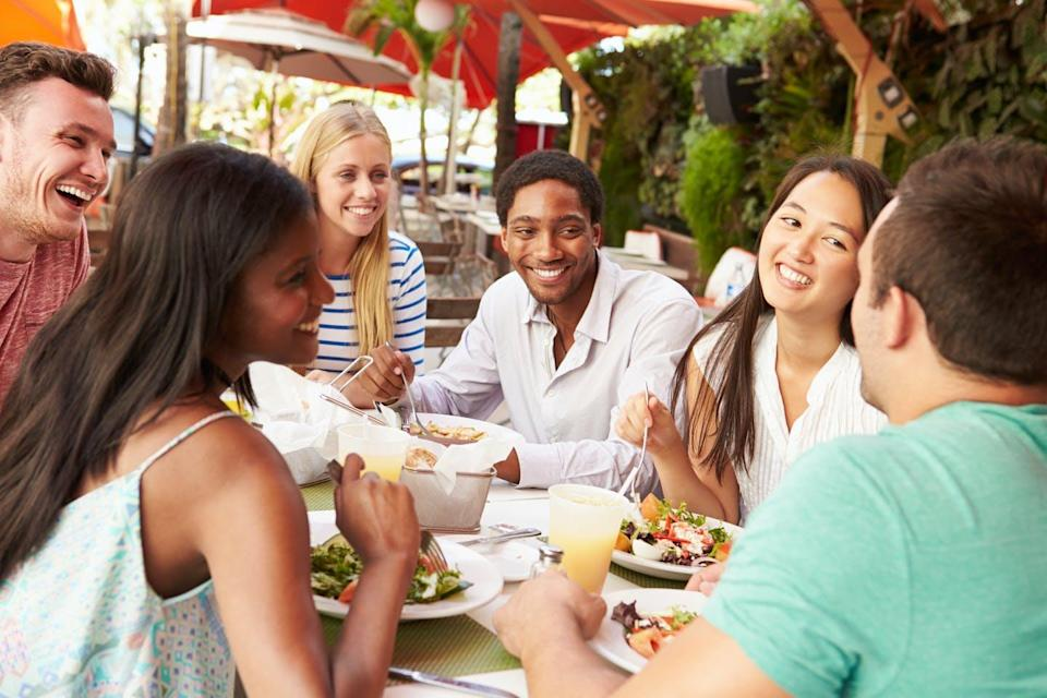 A group of people around an outdoor restaurant table, eating