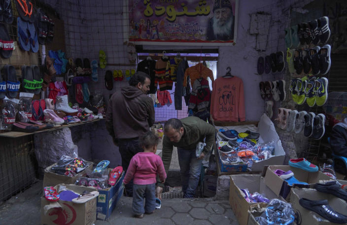 Image: A child tries on new shoes at a street shop display for customers to buy new shoes and clothing, in preparation for the Coptic Christmas celebration, at a residential and industrial area of eastern Cairo, Egypt, Monday, Jan. 6, 2020. (AP Photo/Hamada Elrasam)