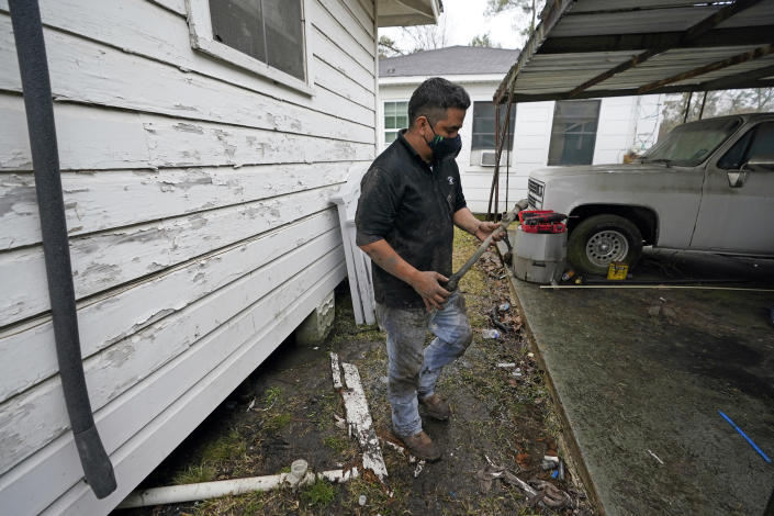 Johnny Vicar, a plumber for West Street Recovery, carries a busted pipe removed from under a home, Thursday, Feb. 25, 2021, in Houston. Many pipes in the area busted during a recent winter storm. (AP Photo/David J. Phillip)