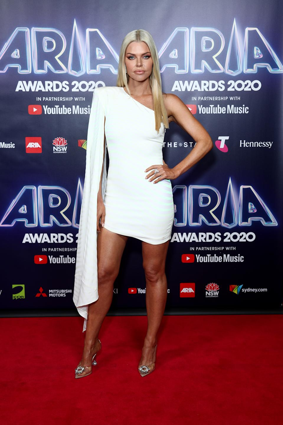 Sophie Monk wears a white one-shouldered mini dress on the red carpet at the 2020 ARIA Awards at The Star on November 25, 2020 in Sydney, Australia.
