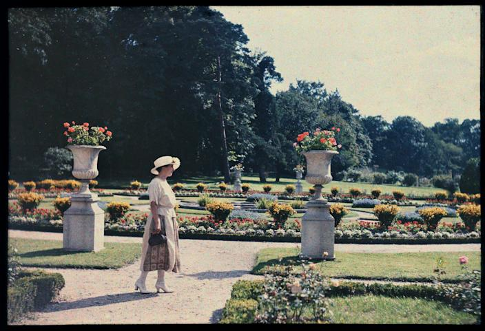 Lady from the parisian bourgeoisie near a flower bed in the jardin de Bagatelle in Paris 1920.