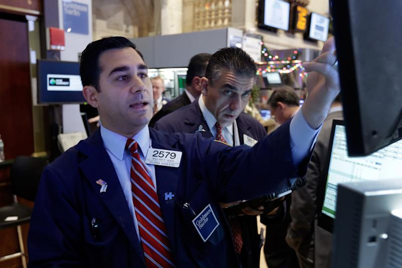 In this Monday, Dec. 16, 2013 photo, specialist William Geier, left, works on the floor of the New York Stock Exchange. Investors took to the sidelines Tuesday, Dec. 17, 2013, a day ahead of a key policy decision from the U.S. Federal Reserve that may see the central bank reduce its massive monetary stimulus. (AP Photo/Richard Drew)