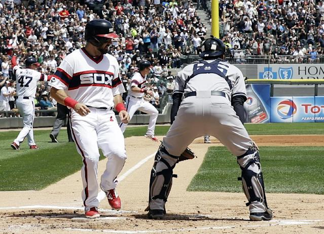 Chicago White Sox's Adam Eaton, left, scores on a double hit by Dayan Viciedo as New York Yankees catcher John Ryan Murphy waits got the ball during the first inning of a baseball game in Chicago on Saturday, May 24, 2014. (AP Photo/Nam Y. Huh)
